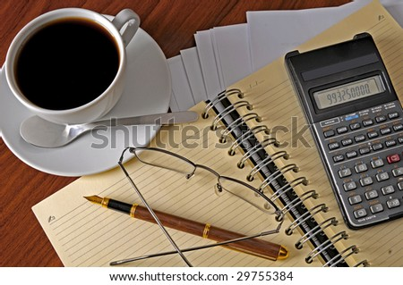 Spiral Notebook, calculator and cup of coffee at workplace - stock photo