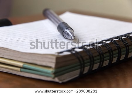 Spiral notebook over the desk with a black pen. - stock photo