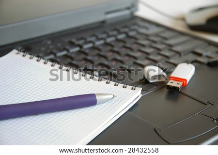 Spiral Notebook, pen and usb flash on laptop keyboard - stock photo
