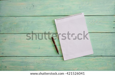 Spiral notebook. White blank notebook on grunge wood - stock photo