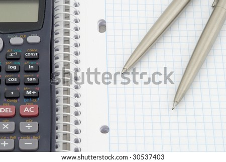 Spiral notebook with blue grid. Calculator, pen and  pencil. Selective focus - stock photo