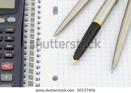 Spiral notebook with blue grid. Calculator, pen, pencil and fountain pen. Selective focus - stock photo