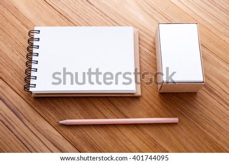Spiral notebook with pencil and business name card on wood table