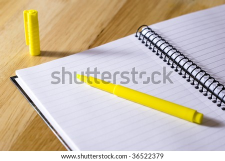 Spiral notebook with yellow highlighter arranged on wooden background - stock photo