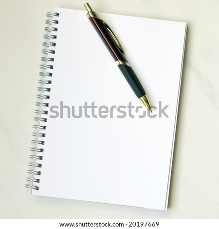 Spiral notepad with pen on marbled desk - stock photo
