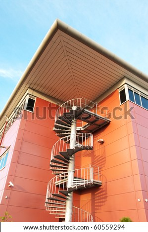 Spiral staircase at corner of modern, brightly-colored office building featuring geometric patterns - stock photo