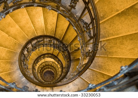 Spiral staircase, forged handrail and stone steps in old tower - stock photo