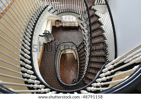 Spiral staircase in luxury home with black railing - stock photo