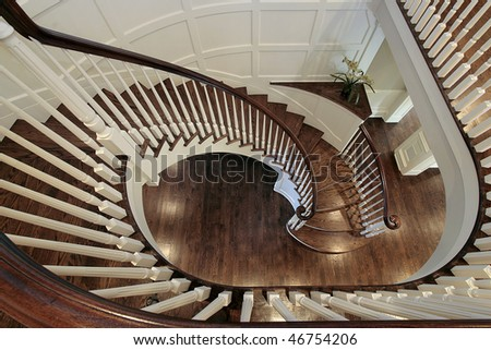 Spiral staircase in luxury home with wood railing - stock photo
