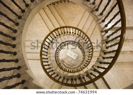Spiral staircase made by white marble and Pine wood handrail. - stock photo