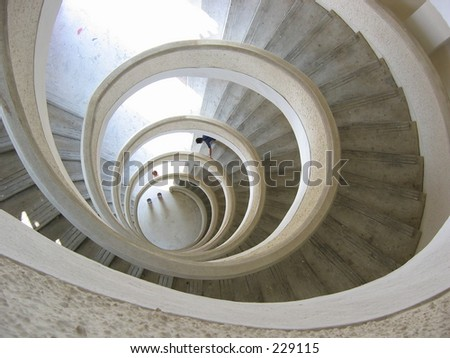 Spiral staircase with a man looking at something near the bottom - stock photo