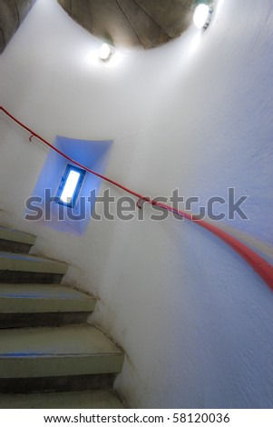 spiral staircase with red handrail and blue light from outside - stock photo