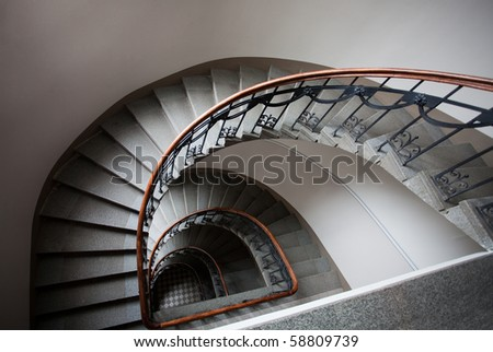 Spiral staircase with wooden handrail in art nouveau house - stock photo
