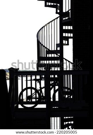 Spiral stairs and a bicycle are silhouetted against the bright summer sky in Rockport, Massachusetts - stock photo