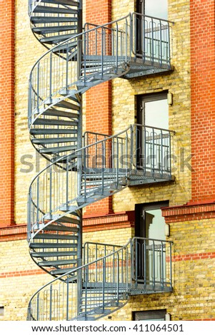 Spiral stairs going from floor to floor outside a yellow and red brick building. Emergency glass doors leading to steps are closed. - stock photo