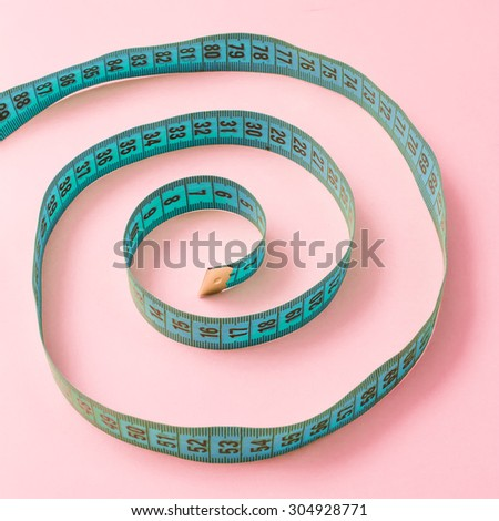 Spiral tailor measuring tape on pink background  - stock photo