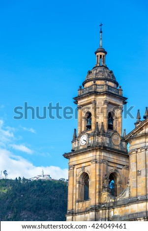 Spire of the primary cathedral in Bogota, Colombia with Monserrate visible in the background - stock photo