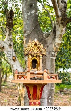 spirit house in thailand with garland and some wreathes, joss house - stock photo