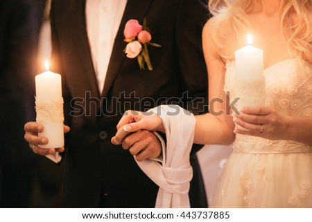 Spiritual emotional bride taking vows hands ties together in christian church closeup
