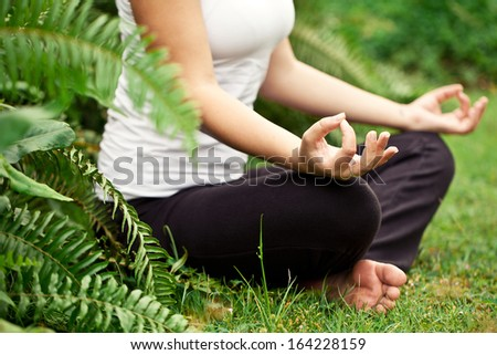 Spiritual fit woman sitting in lotus pose on a river stone
