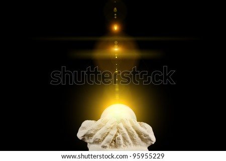 Spiritual healing light in cupped hands on a black background - stock photo
