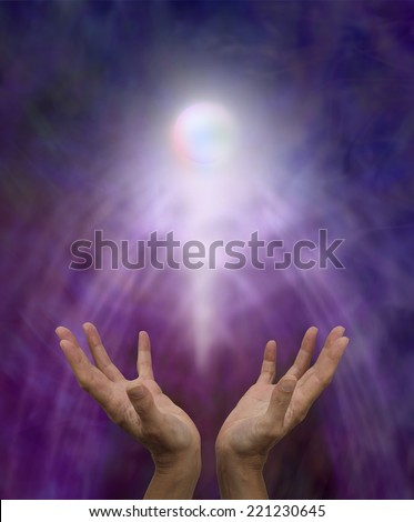 Spiritual Healing Orb  -  Healer's outstretched open hands with a glowing spirit orb rising up on a misty purple and blue background - stock photo