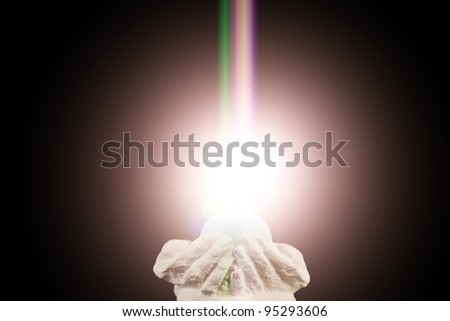 Spiritual light in cupped hands on a black background - stock photo