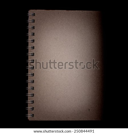Spiritual or esoteric concept - close up on dimmed dark brown cardboard  notebook on deep black background