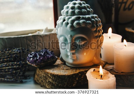 spiritual ritual meditation face of Buddha ametist candles on old wooden background - stock photo