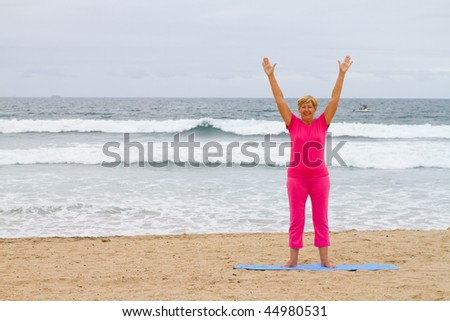 spiritual senior woman on beach