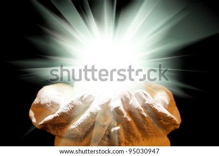 Spiritual white light in cupped hands on a black background - stock photo