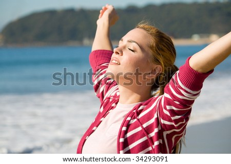 spiritual woman with arms open wide on beach - stock photo