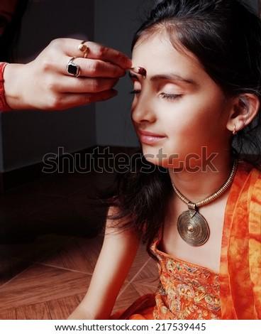 Spirituality- Human hand putting red kumkum on forehead. - stock photo