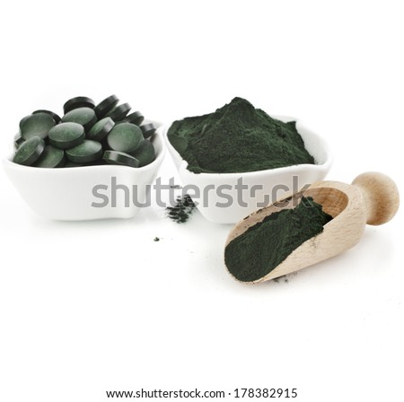 Spirulina algae  powder and tablets in spoon , isolated on white background  - stock photo