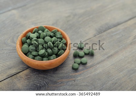 Spirulina in pills over black wooden background - stock photo