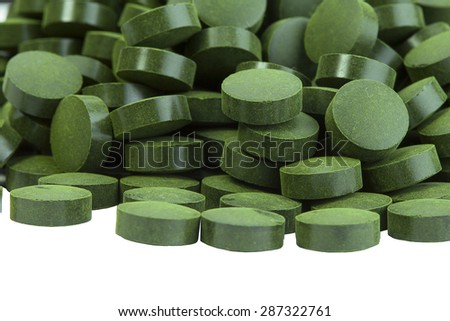 Spirulina tablets algae nutritional supplement heap surface close up top view, isolated on white background
