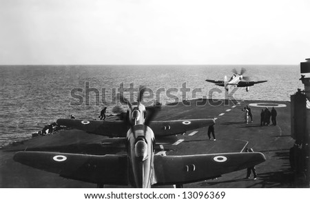 Spitfire or Hurricane aircraft scrambling off the deck of HMS Illustrious in WWII in the Med