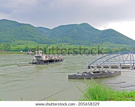 SPITZ AN DER DONAU, AUSTRIA - 16 July 2014: A ferry is crossing the river Danube. The Wachau Cultural Landscape is an excursion destination and a UNESCO World Heritage.  - stock photo