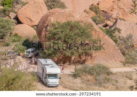 SPITZKOPPE, NAMIBIA - JUNE 5, 2011: Unidentified rock climbers scaling a huge boulder at a camp site at Spitzkoppe