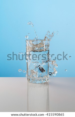 Splash from ice cube in a glass of water, on the nature blue background