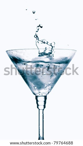 Splash from ice cube in martini glass isolated - stock photo
