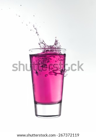 Splash in a glass of pink lemonade isolated on white background - stock photo