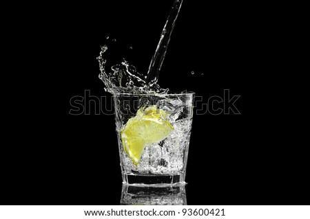 splash in a glass with lemon and ice on a black background - stock photo