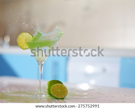 splash in glass of margarita on the bar - stock photo