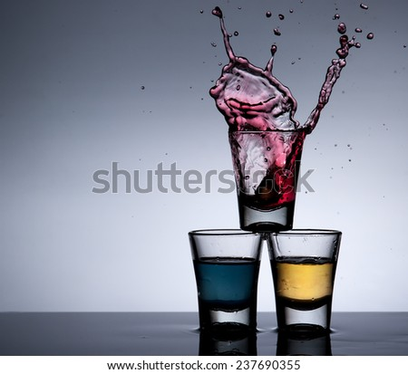 Splash of alcohol cocktail and glass ,dark background - stock photo