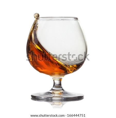 Splash of cognac in glass isolated on white background - stock photo