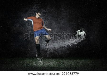 Splash of drops around football player under water - stock photo