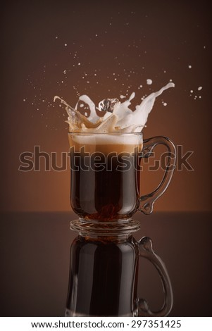 Splash of  ice coffee drink on a brown background. Refreshing Iced cappuccino liquid drink pouring into a mug, cup with ice cubes. Cold beverage wave. Close-up design liquor milk, coffee and ice.   - stock photo