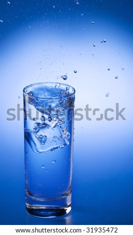 Splash of mineral water and  falling ice cube into a transparent glass over blue gradient background
