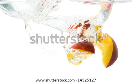 Splash of peach slices in the water. - stock photo